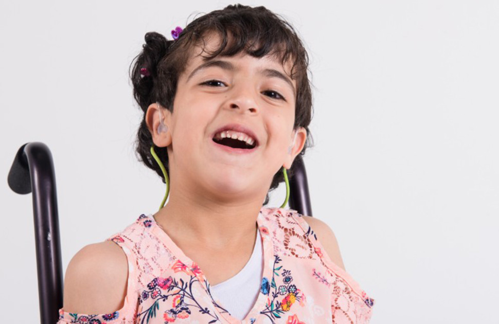 Girl in wheelchair smiling at camera